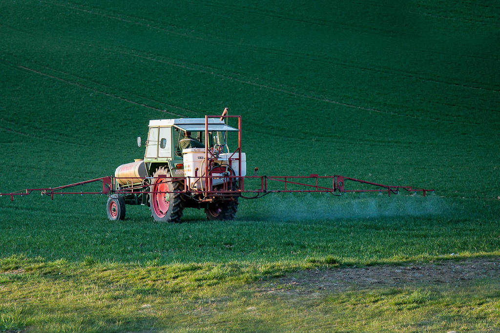 cesta organica agricultor aplicando uso de agrotoxico